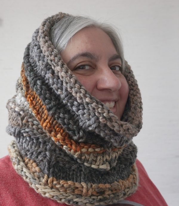 Free knitting pattern: Rustic Hooded Cowl in Lion Brand Mandala Thick & Quick yarn by Underground Crafter | smiling woman wearing textured, hooded cowl looking to the right