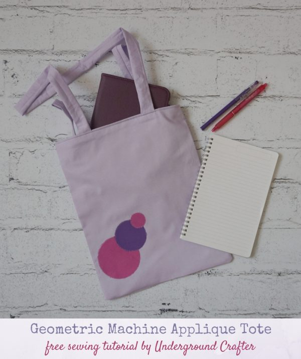 Geometric Machine Applique Tote, free sewing pattern by Underground Crafter - flatlay photo with tote bag with circular appliques, notebook, tablet, and pens on faux brick backdrop