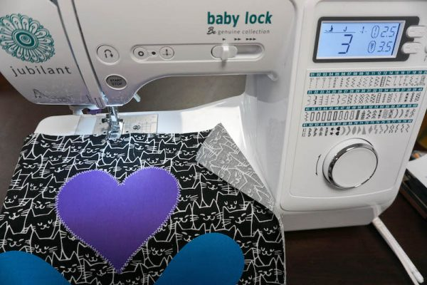 Geometric Machine Applique Tote, free sewing pattern by Underground Crafter - appliqued hearts on cat fabric against Baby Lock Jubilant sewing machine