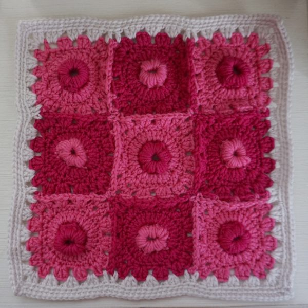 Great Star Coral Square, free 12 inch free crochet granny square pattern by Underground Crafter | textured granny square on white-painted wood surface