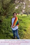 Free crochet triangular shawl pattern: It's a Colorful Summer Shawl in Lion Brand Mandala for Itchin' for Some Stitchin' for Underground Crafter | Woman wearing rainbow shawl outside against greenery