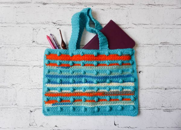 Caribbean Sunset Bag, free crochet pattern in Paintbox Yarns Chunky Pots and Simply Chunky yarns by Underground Crafter | flat lay photo of textured, striped bobble crochet bag on faux brick background with tablet, crochet hook, and pens