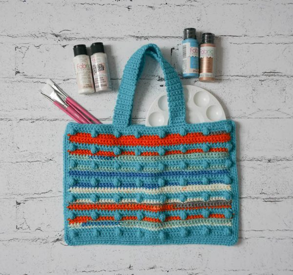 Caribbean Sunset Bag, free crochet pattern in Paintbox Yarns Chunky Pots and Simply Chunky yarns by Underground Crafter | flat lay photo of textured, striped bobble crochet bag on faux brick background with craft paint supplies