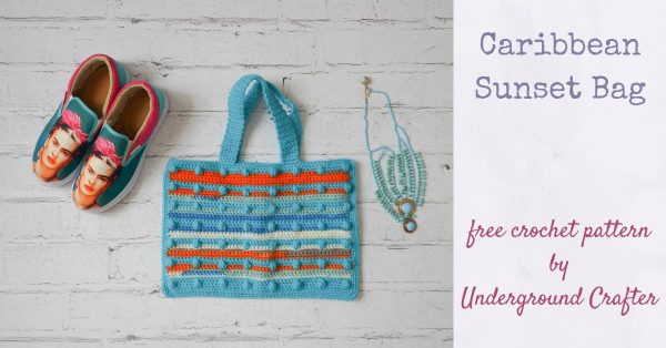 Caribbean Sunset Bag, free crochet pattern in Paintbox Yarns Chunky Pots and Simply Chunky yarns by Underground Crafter | flat lay photo of textured, striped bobble crochet bag on faux brick background with Frida Kahlo shoes and dangling stone necklace
