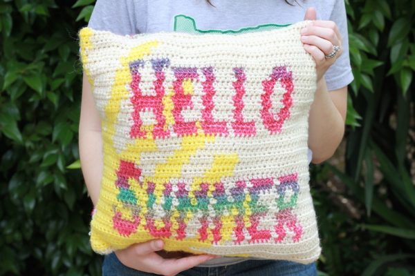 "Hello Summer Pillow, free tapestry crochet pattern by E'Claire Makery for Underground Crafter - handmade pillow with sun and words ""hello summer"" in tapestry crochet held in arms in front of greenery"