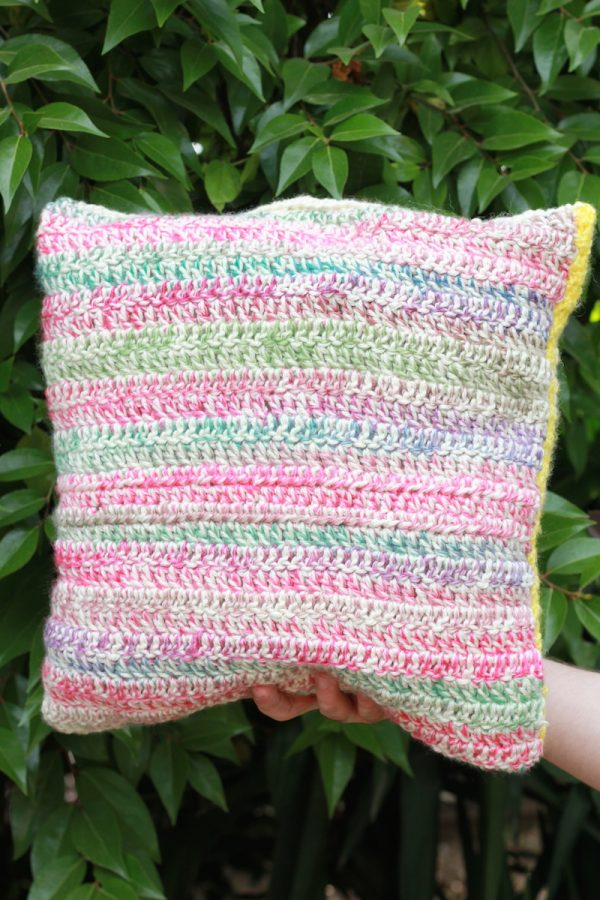 Hello Summer Pillow, free tapestry crochet pattern by E'Claire Makery for Underground Crafter - multicolored crochet pillow held in hand in front of greenery