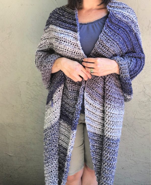 Storm Ridge Wrap, free crochet pattern in Red Heart Roll With It Tweed by ChristaCoDesign for Underground Crafter - crochet wrap draped over woman's body with hands clasped