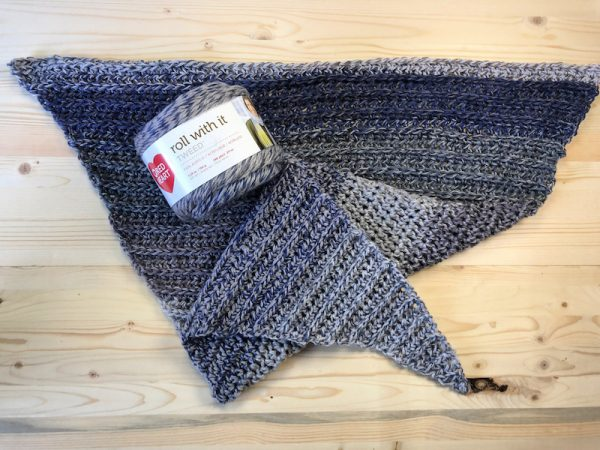 Storm Ridge Wrap, free crochet pattern in Red Heart Roll With It Tweed by ChristaCoDesign for Underground Crafter - crochet wrap against wood with yarn