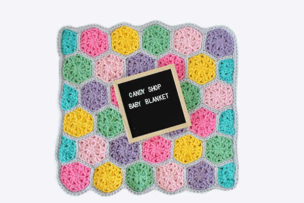 Colorful crochet hexagon blanket laid flat with letterboard sign on top - Candy Shop Baby Blanket, free crochet pattern in Paintbox Yarns Wool Mix Super Chunky yarn by The Blue Elephants for Underground Crafter
