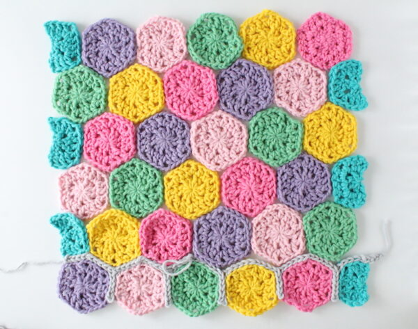Colorful crochet hexagons displayed before joining - Candy Shop Baby Blanket, free crochet pattern in Paintbox Yarns Wool Mix Super Chunky yarn by The Blue Elephants for Underground Crafter