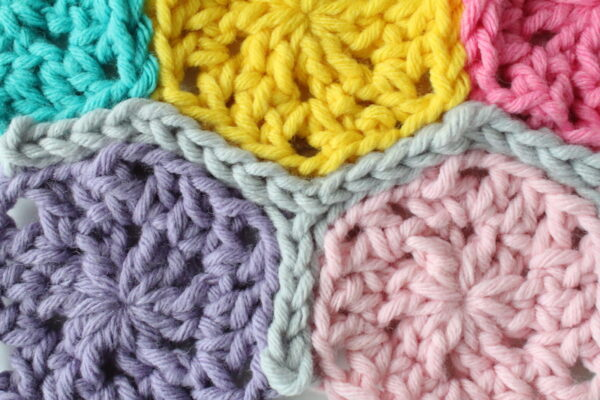 Detail of slip stitch join of colorful hexagon crochet blanket - Candy Shop Baby Blanket, free crochet pattern in Paintbox Yarns Wool Mix Super Chunky yarn by The Blue Elephants for Underground Crafter