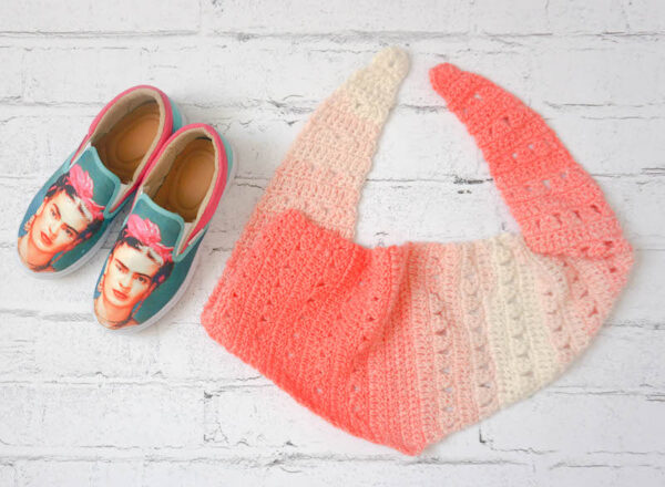 Crocheted, striped triangle scarf in coral and cream yarn with sneakers with Frida Kahlo images on them on painted white brick background - Fro Yo Triangle Scarf, free crochet pattern in Lion Brand Scarfie yarn by Underground Crafter