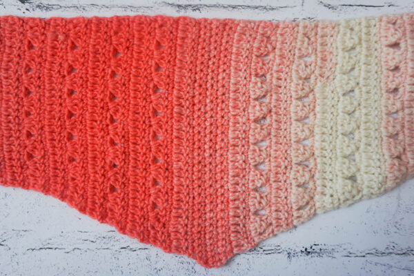 Crocheted, striped triangle scarf in coral and cream yarn on painted white brick background - Fro Yo Triangle Scarf, free crochet pattern in Lion Brand Scarfie yarn by Underground Crafter