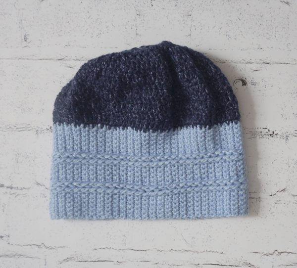 Free crochet pattern: On the Right Tracks Beanie in Lion Brand Jeans yarn by Underground Crafter - blue striped crochet hat on white, faux brick background