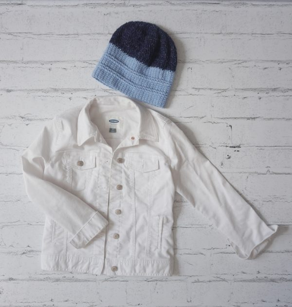 Free crochet pattern: On the Right Tracks Beanie in Lion Brand Jeans yarn by Underground Crafter - blue striped crochet hat on white, faux brick background with white jeans jacket