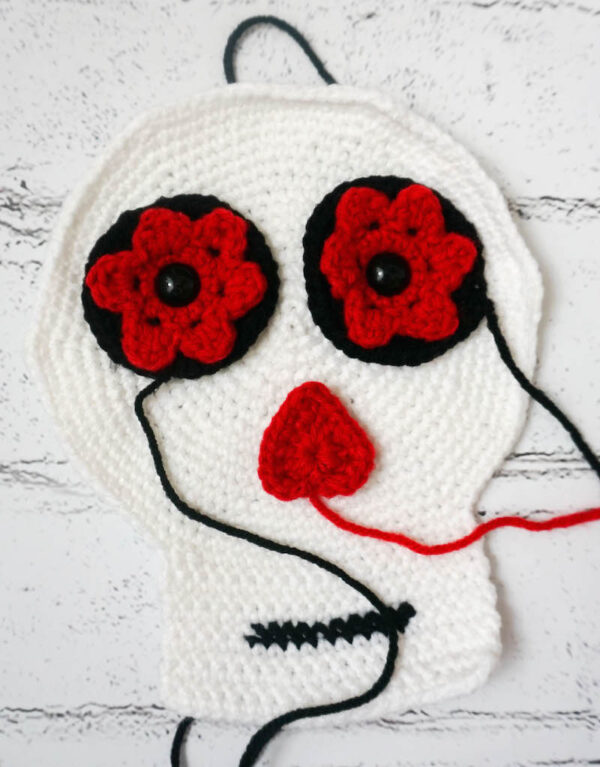 Crochet sugar skull with eyes and nose with yarn attached ready for assembly - Simple Skull - Sugar Skull Reversible Softie free crochet pattern by Underground Crafter
