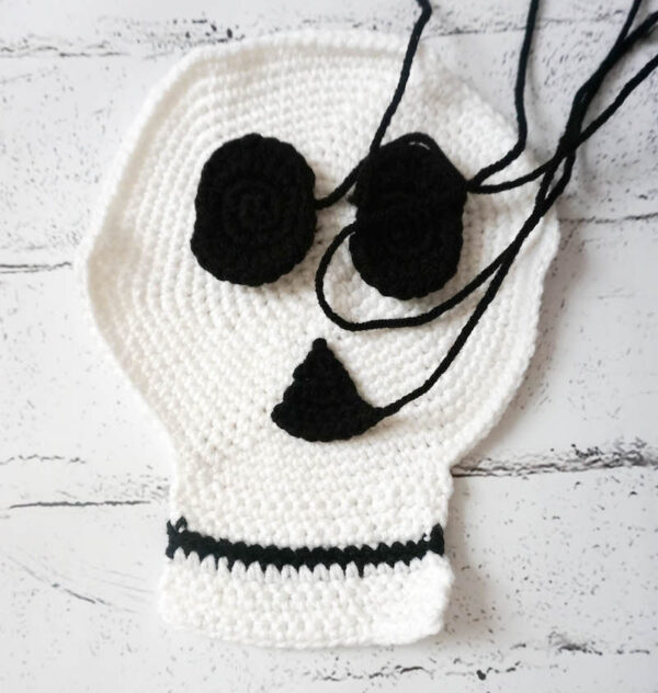 Crochet skull with eyes and nose with yarn attached ready for assembly - Simple Skull - Sugar Skull Reversible Softie free crochet pattern by Underground Crafter