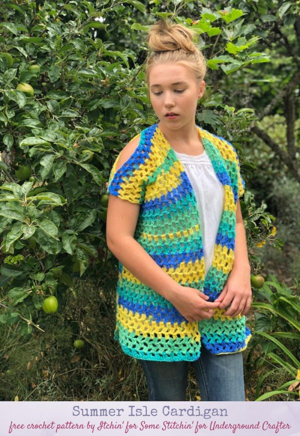 Free crochet pattern: Summer Isle Cardigan by Itchin' for Some Stitchin' in Red Heart Bunches of Hugs yarn for Underground Crafter - woman wearing striped, sleeveless crochet cardigan, standing against greenery