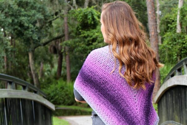 Summer Sunset Shawl, free crochet pattern in Lion Brand Wrap Star yarn by Two Brothers Blankets for Underground Crafter | Woman wearing striped triangular shawl with her back to camera in front of trees