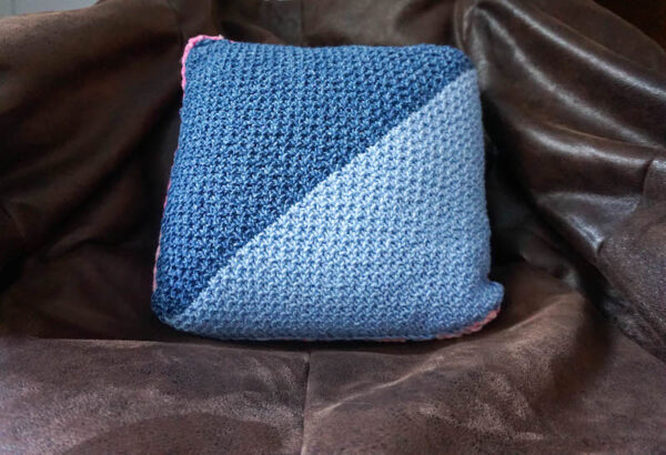 blue knit pillow against faux leather chair - Diagonal Sand Stitch Pillow free knitting pattern in Lion Brand Jeans and Crayola Cake yarn by Underground Crafter